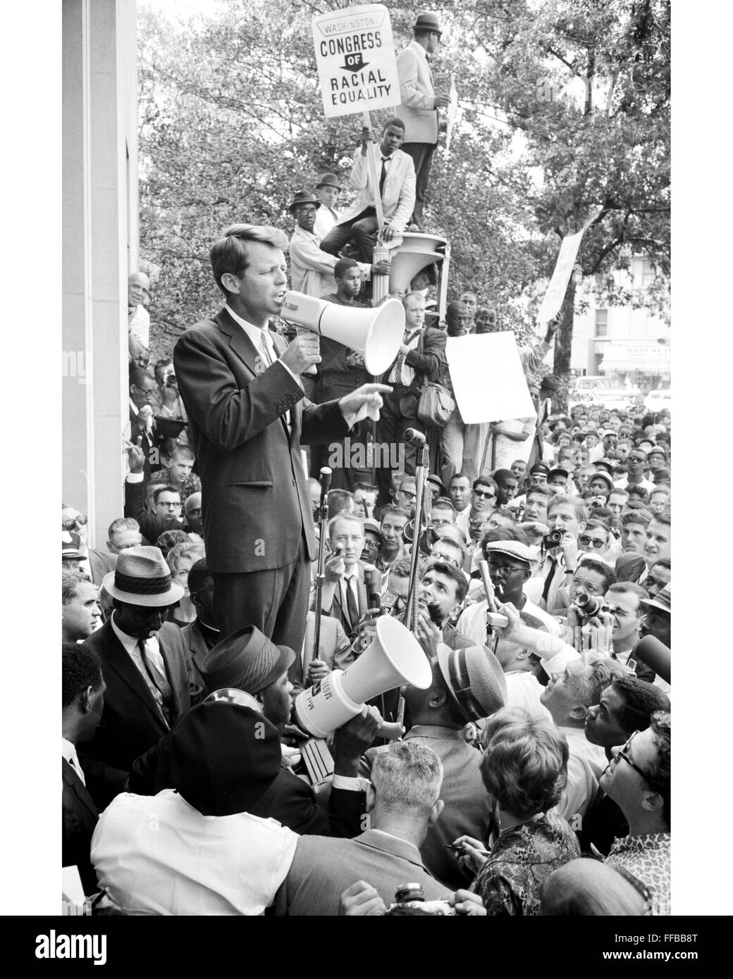U.S. Attorney General Robert F. Kennedy speaks to a crowd of African Americans and whites through a megaphone outside - Stock Image