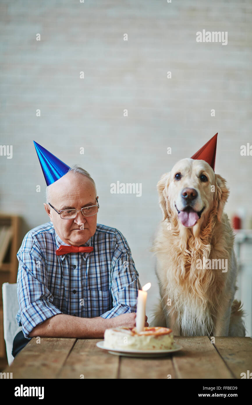 Mature man and his pet sitting by table with birthday cake with burning candle - Stock Image