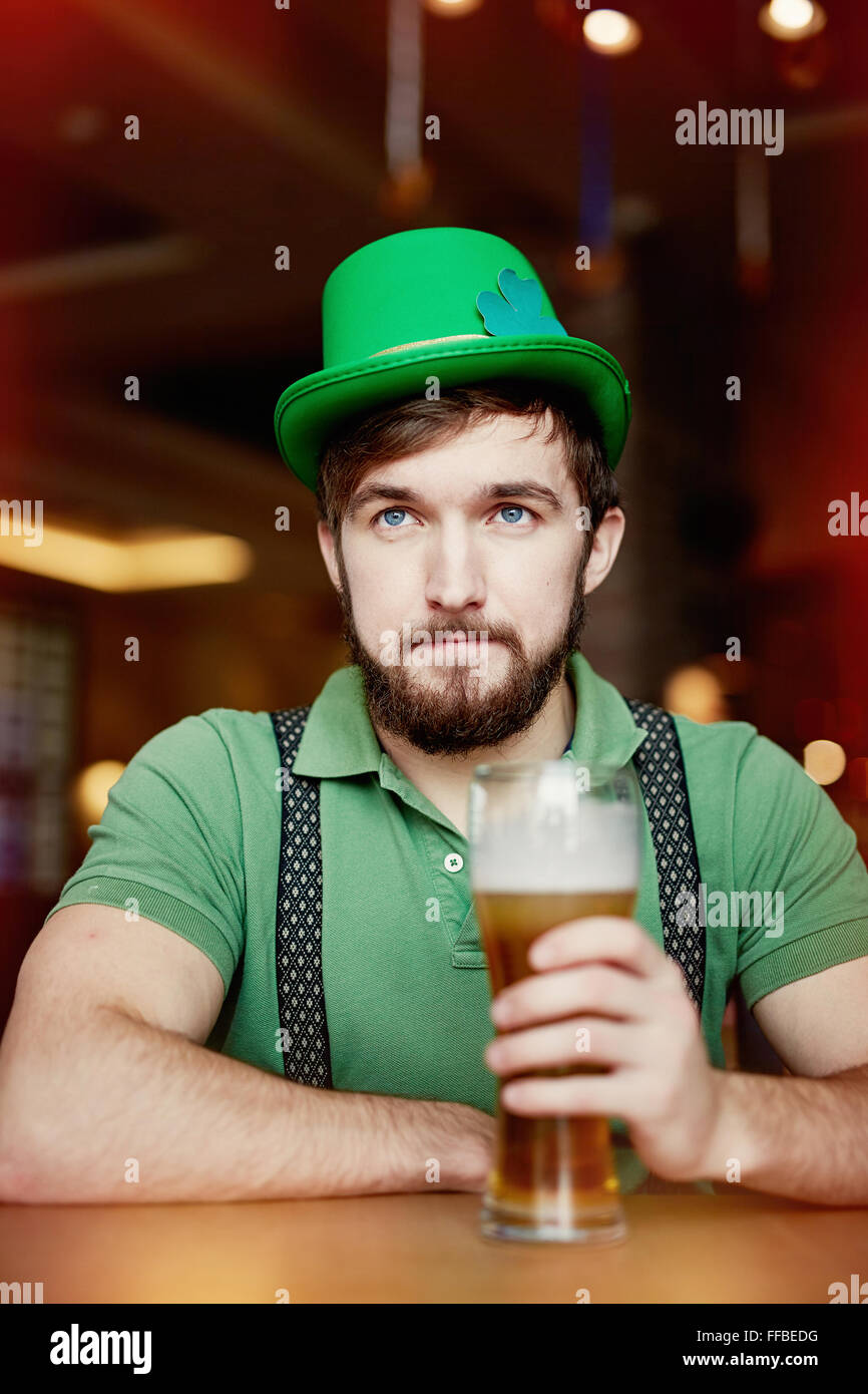 Young man in green hat and T-shirt sitting in pub with glass of beer - Stock Image