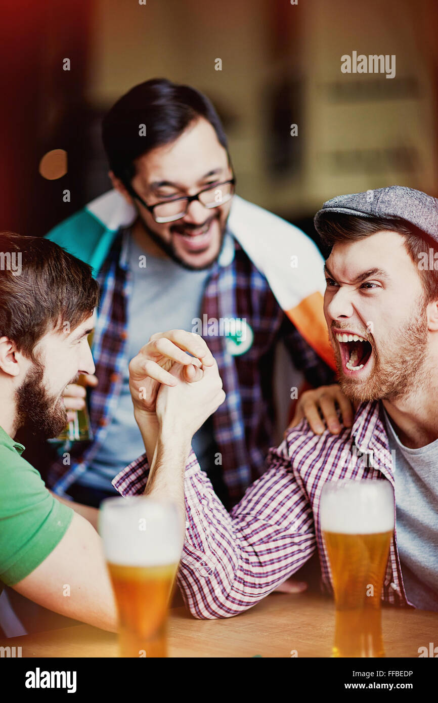Ecstatic fans expressing their gladness upon victory in pub - Stock Image