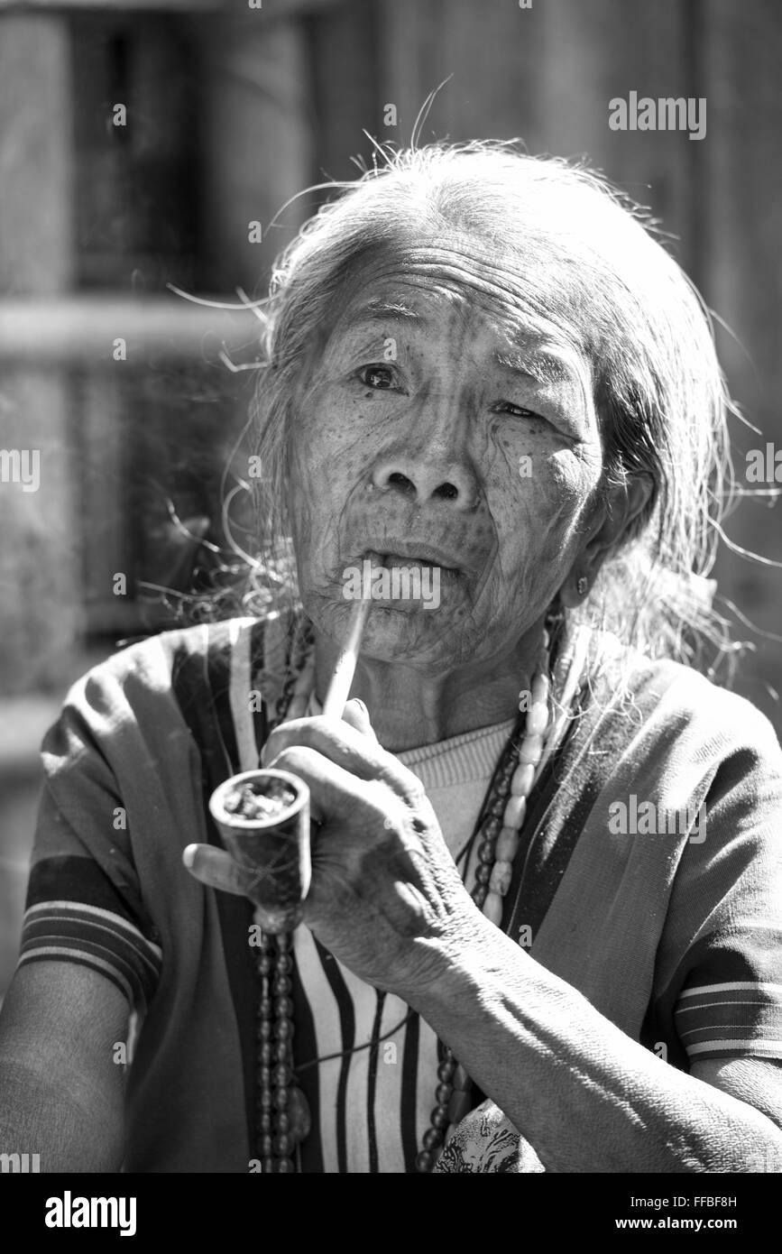 A Muun Chin woman with face tattoos smoking a corncob pipe, Kyar Daw, Mindat, Myanmar The tribal Chin women had - Stock Image