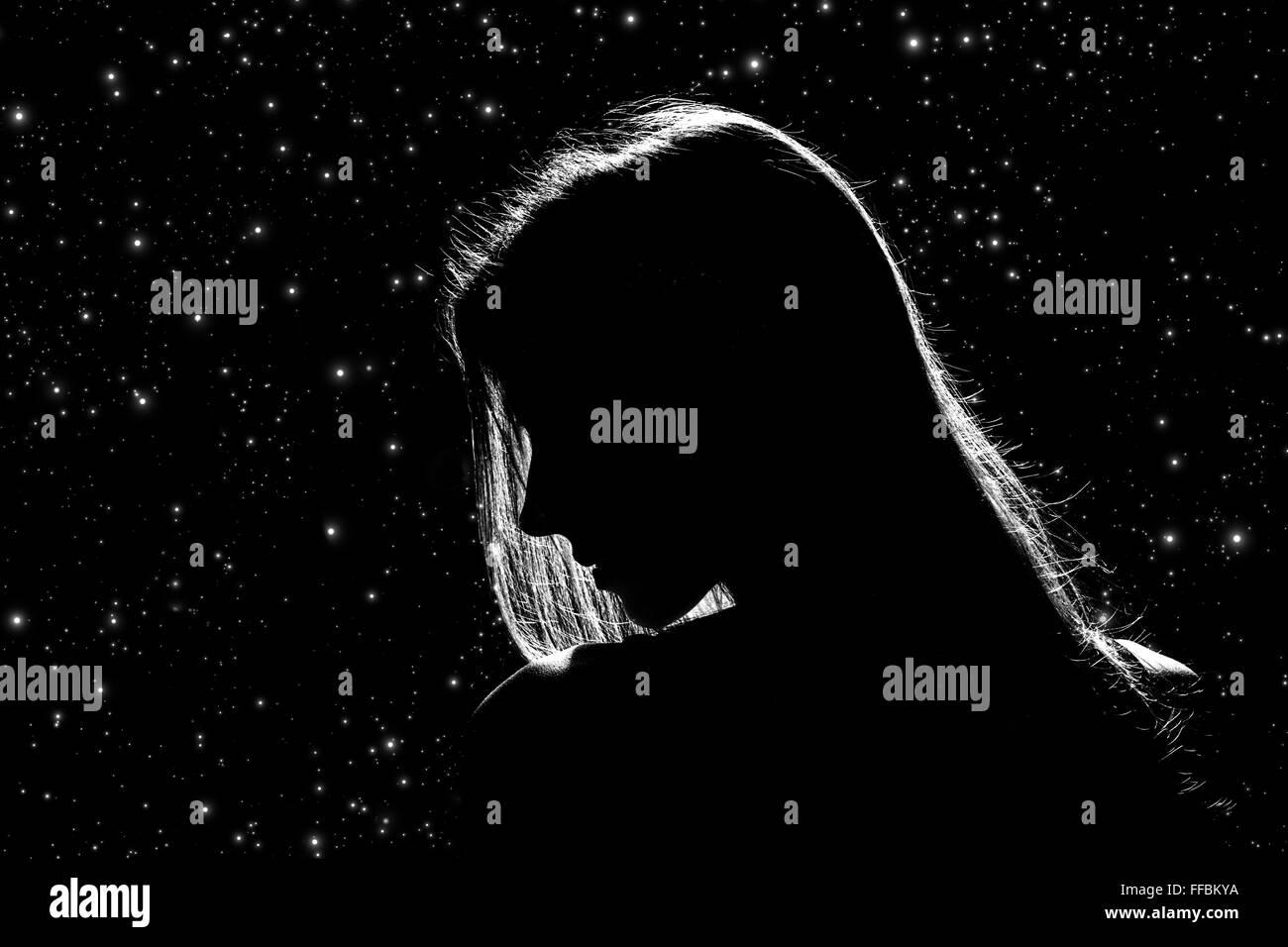 sad female profile silhouette on stars sky, monochrome image - Stock Image