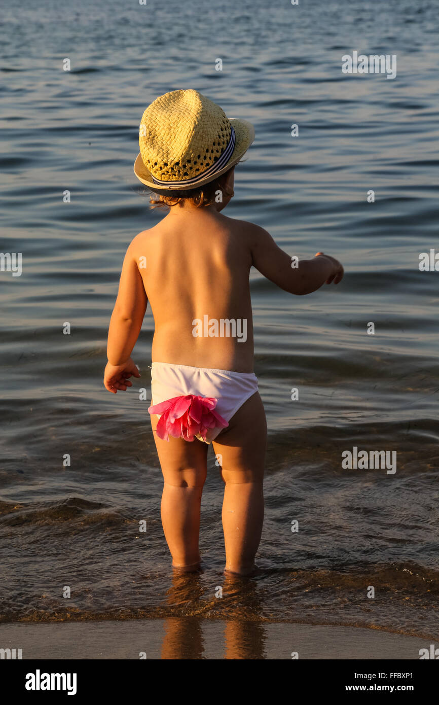 young small child getting into the sea while wearing a hat shoot from the back - Stock Image