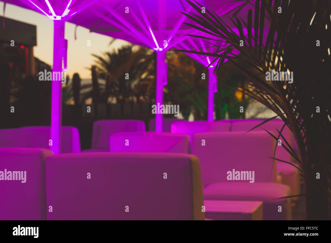 outdoor cafe by night illuminated with neon lights stock photo