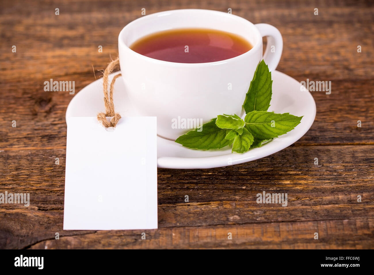 Cup of tea with green leaves and blank label - Stock Image