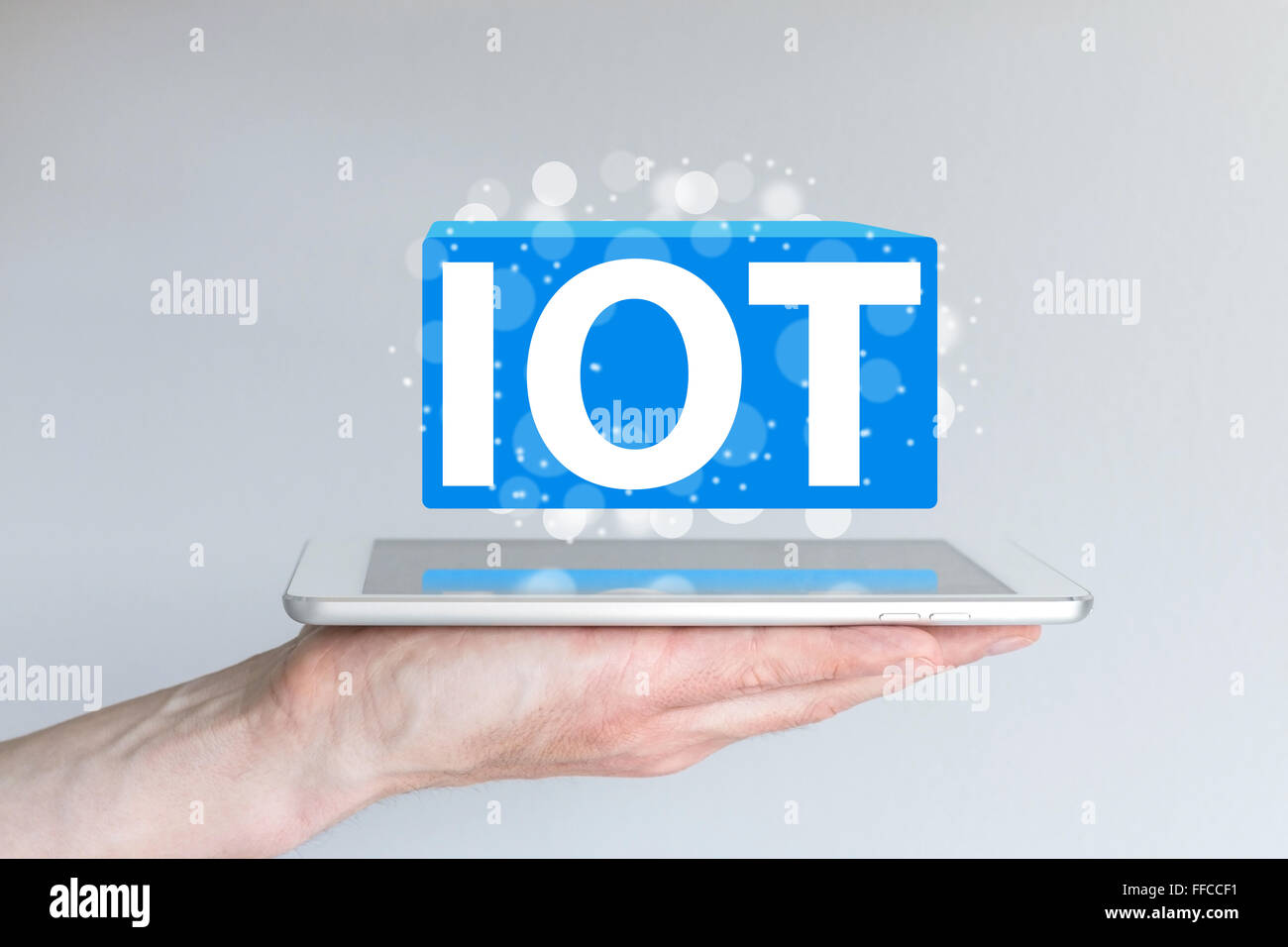 IOT (internet of things) concept and information technology background. Hand holding modern smart phone or tablet - Stock Image