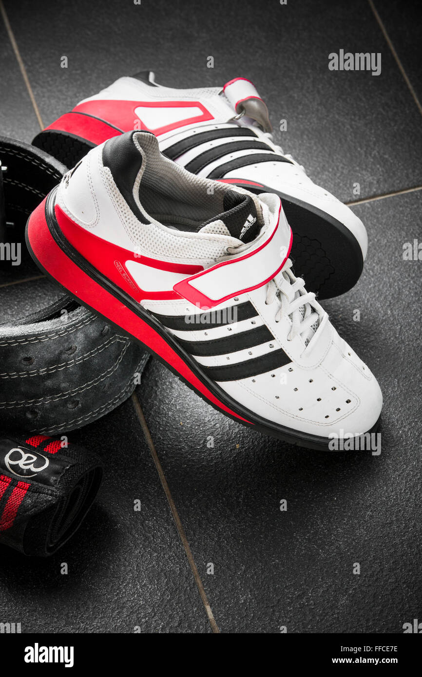 Adidas Olympic weightlifting shoes on a grey tiled floor with a weightlifting belt and wrist straps. - Stock Image