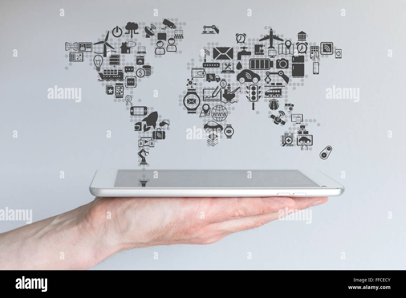 Global mobile devices and internet of things concept. Hand holding modern tablet or smart phone with neutral background. - Stock Image