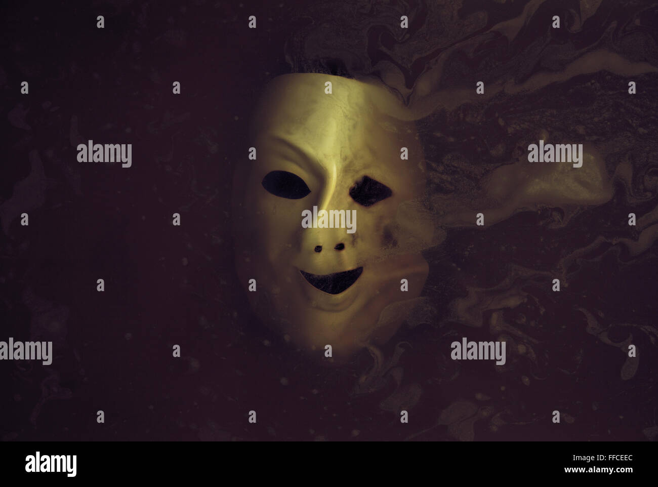 Deformed scary mask in the dark water - Stock Image