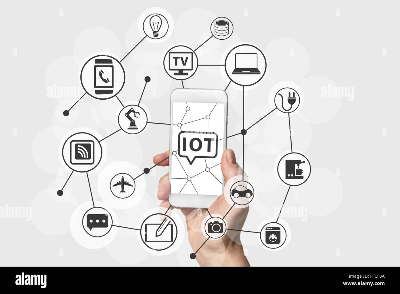 Internet of Things (IOT) concept with hand holding modern white and silver smart phone. Connected devices in the - Stock Image