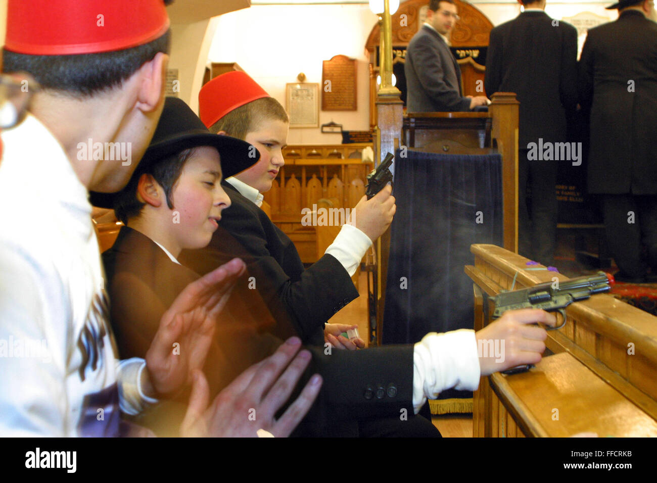 Young Orthodox Jewish boy shoot cap guns and bang on drums every time Haman is mentioned in the congregation during - Stock Image