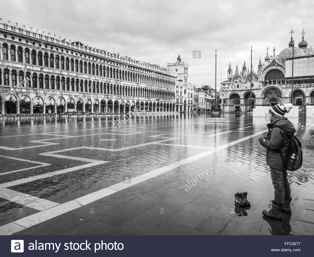 VENICE, ITALY -  24 JANUARY 2013:  Monochrome image of a tourist contemplating crossing a flooded St Mark's - Stock Image