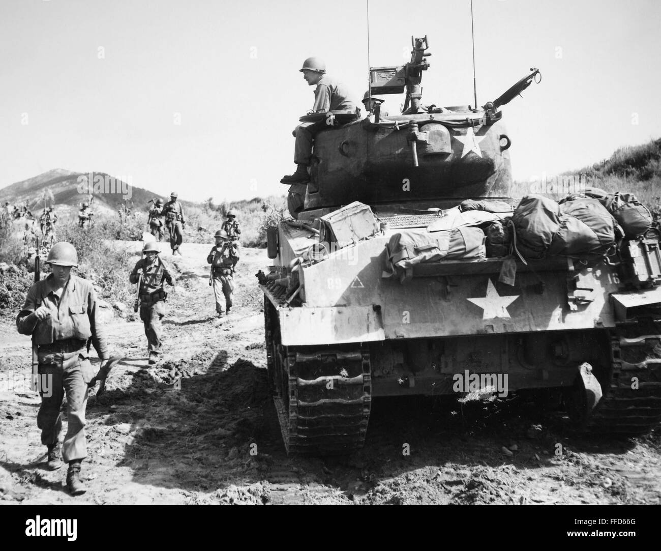 KOREAN WAR: ADVANCING. /nU.S. Army infantrymen, carrying rifles and shovels, and a tank advance toward Communist Stock Photo
