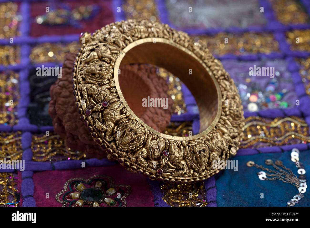 Gold bangle with very heavy indian design - Stock Image