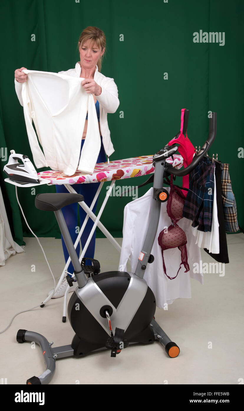 Woman ironing clothes using exercise bike as a clothes horse to hang the clothing - Stock Image