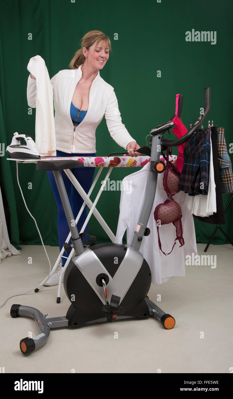 Woman ironing clothes using exercise bike as a clothes horse - Stock Image