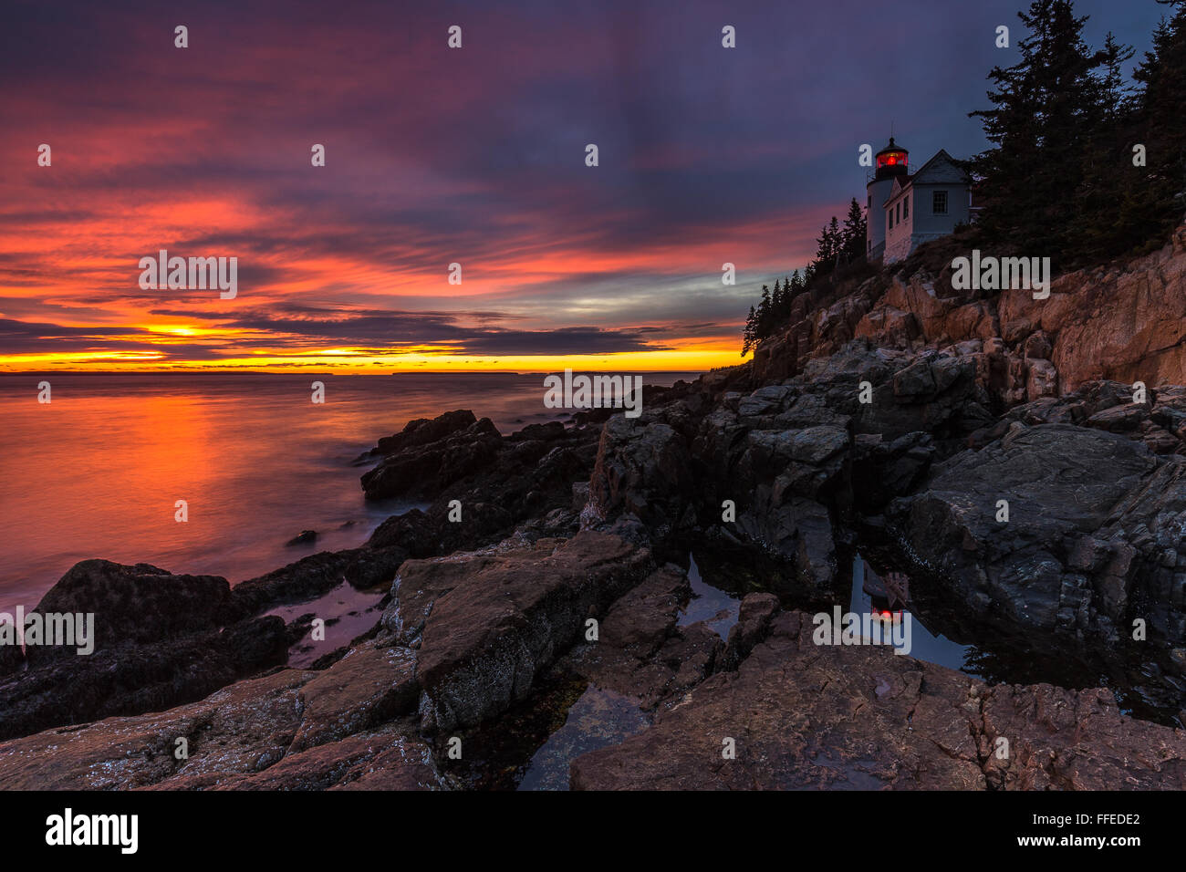 The iconic landmark, Bass Harbor Head Lighthouse reflected in a tidepool at sunset in Acadia National Park, Mount Stock Photo