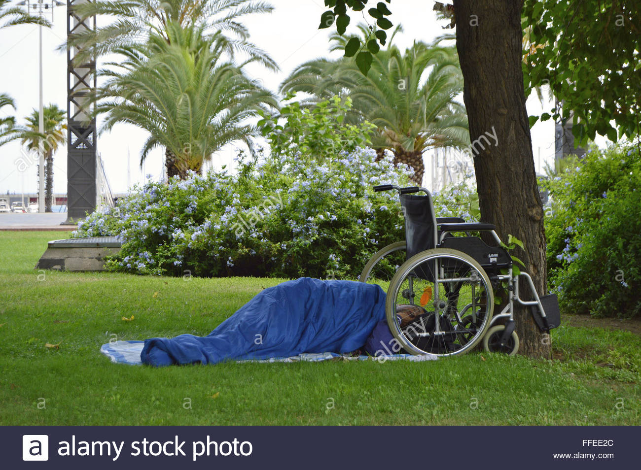Homeless disabled man with wheelchair sleeping in the park, Barcelona Spain Europe - Stock Image