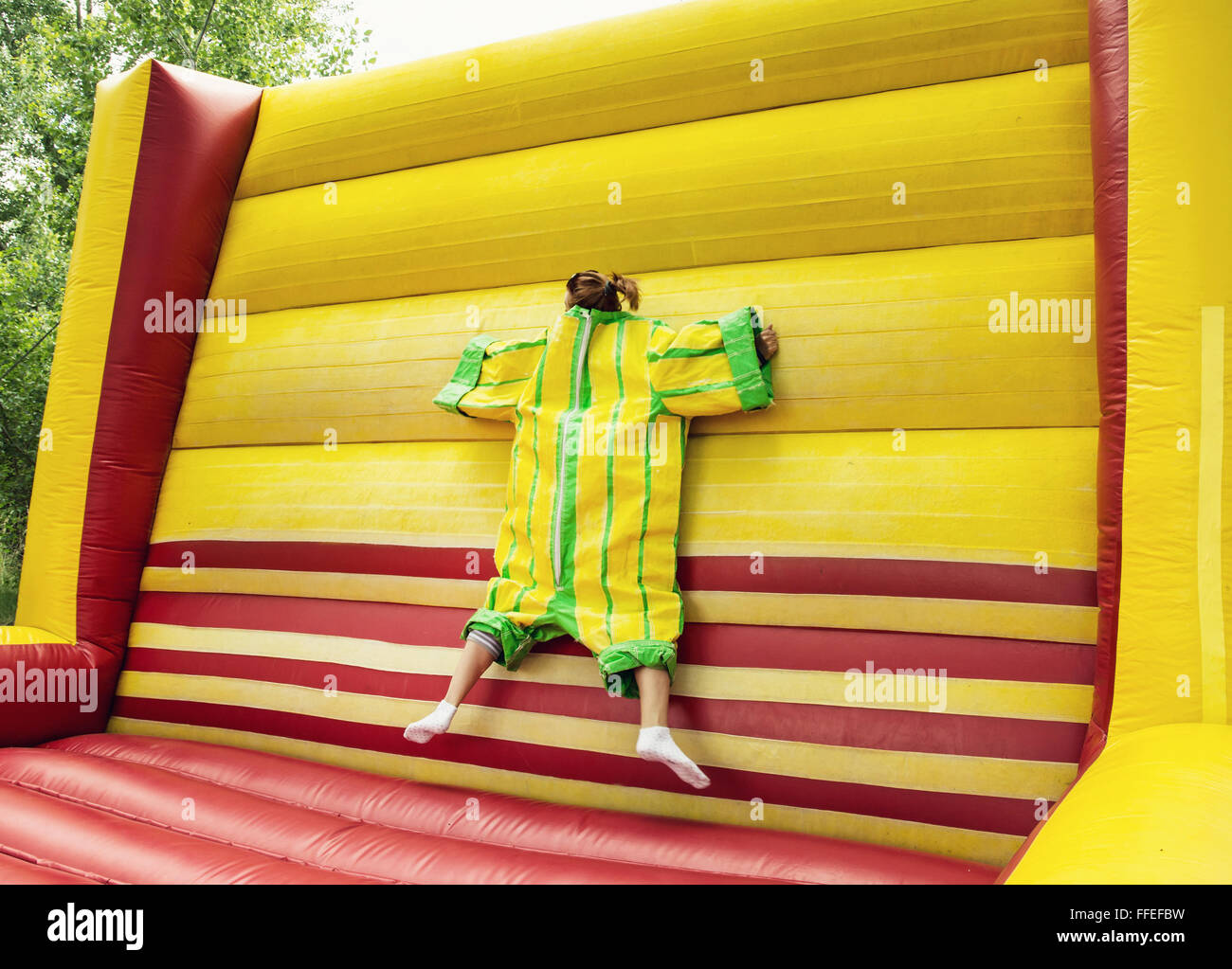 Young woman in plastic dress in a bouncy castle imitates a fly on velcro wall. Inflatable attraction. Leisure activity. - Stock Image
