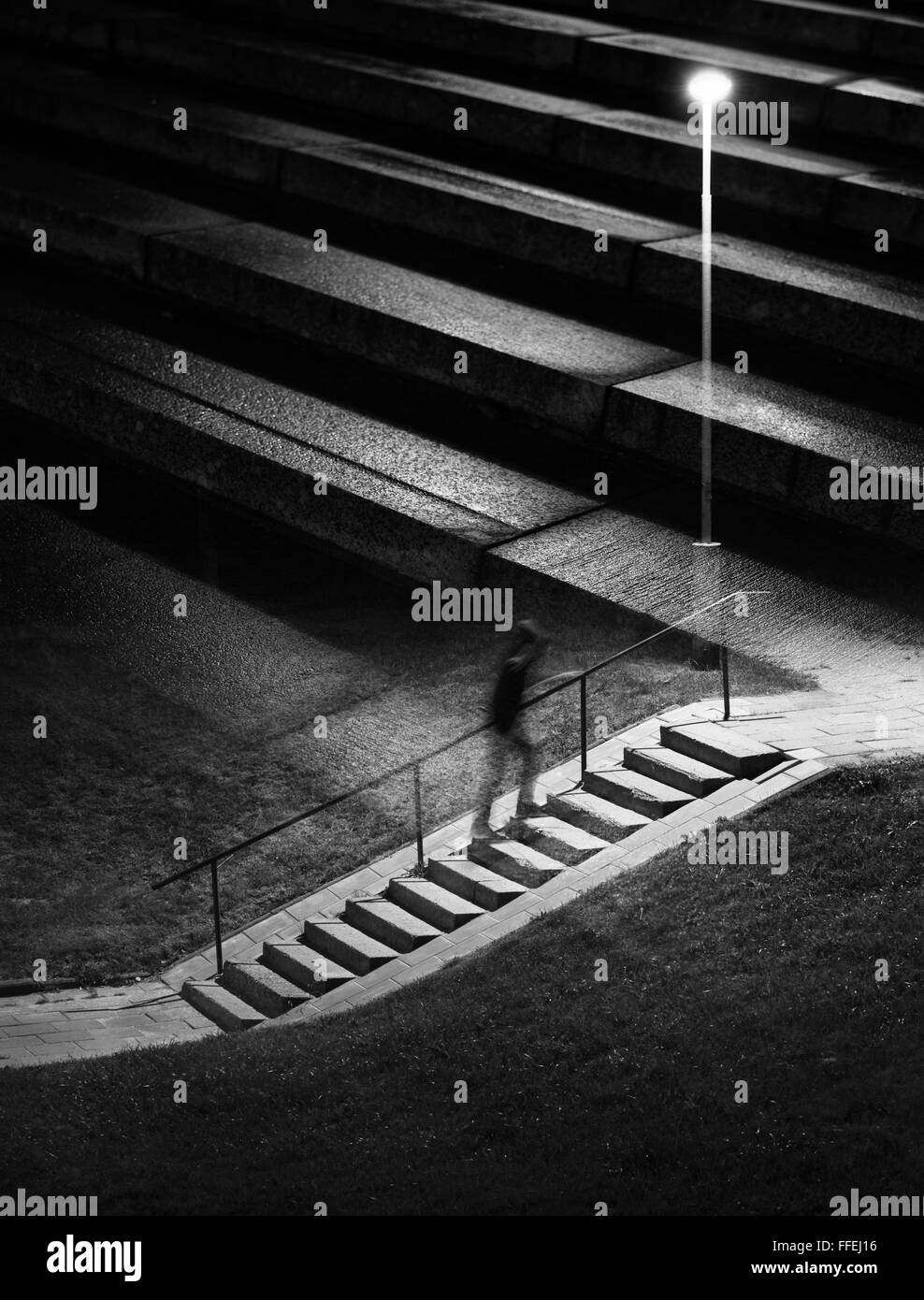 Double exposure night scene. Human figure in motion blur walking up stairs. - Stock Image