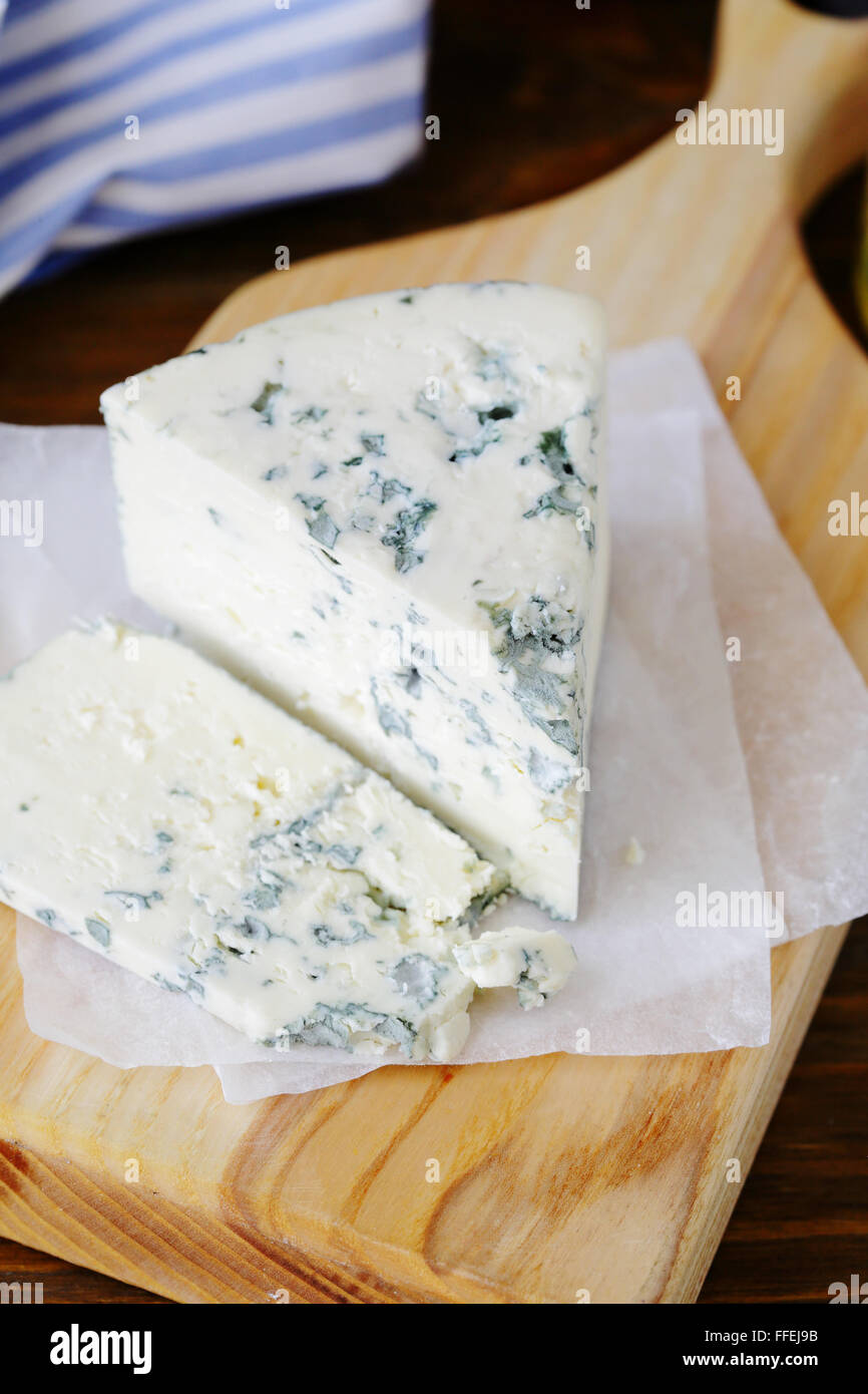 blue cheese on cutting board, food closeup - Stock Image