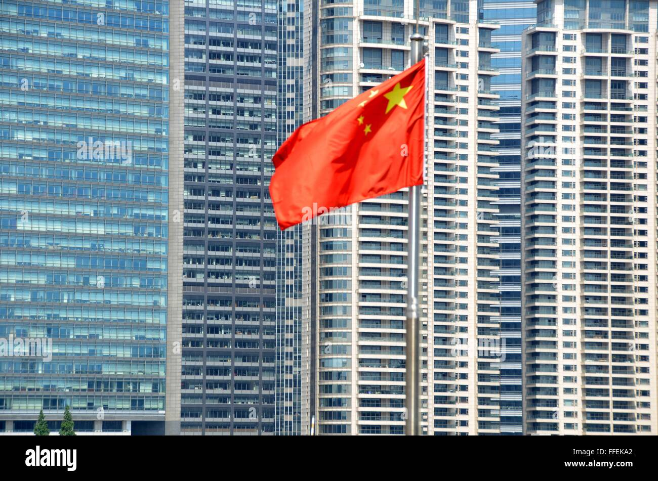 A chinese flag in front of apartment and office buildings in Shanghai - Stock Image