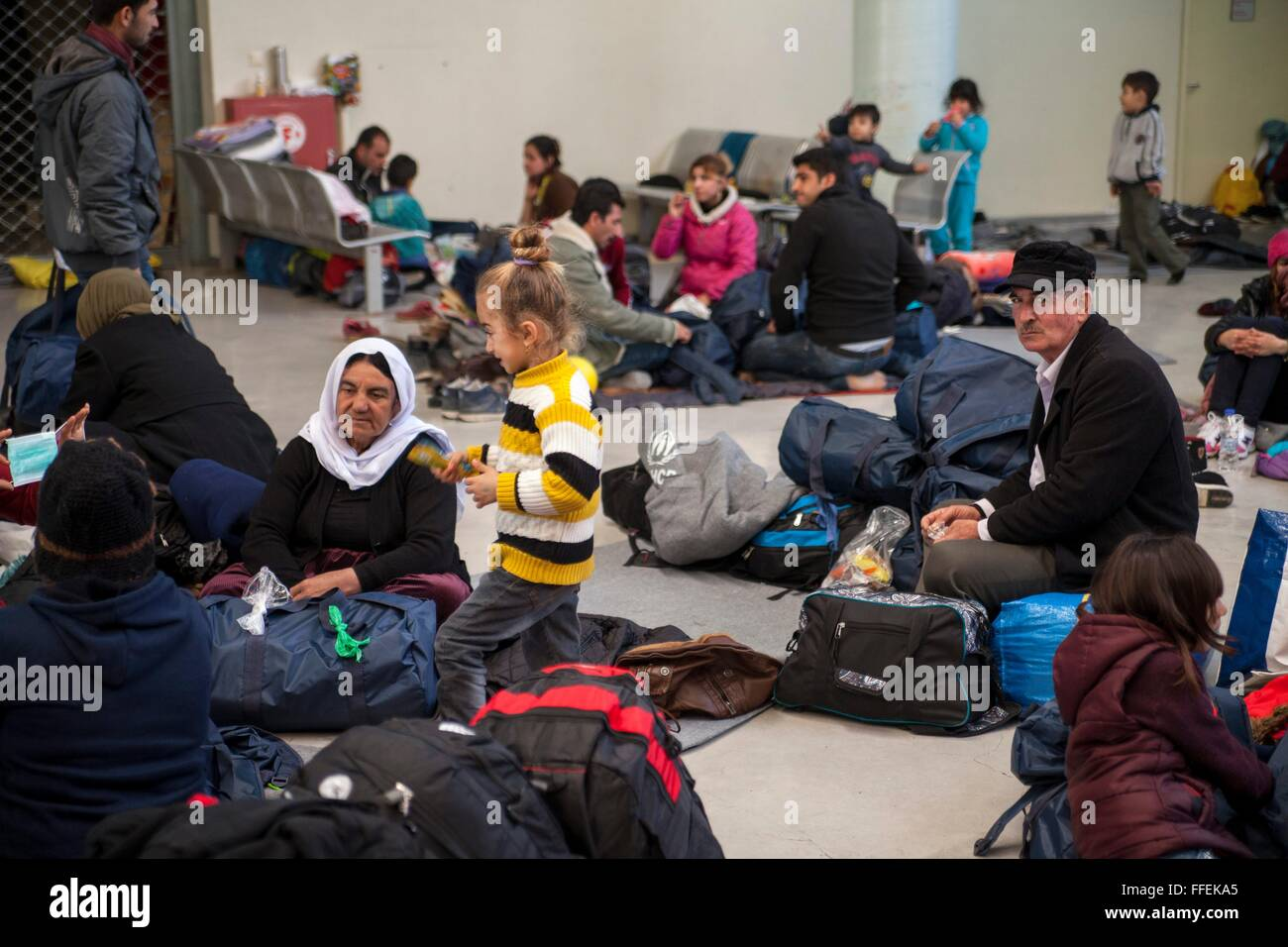 Refguees wait for days within building at habour of Pireaus. Despite difficulties in Greece, families hope to continue - Stock Image