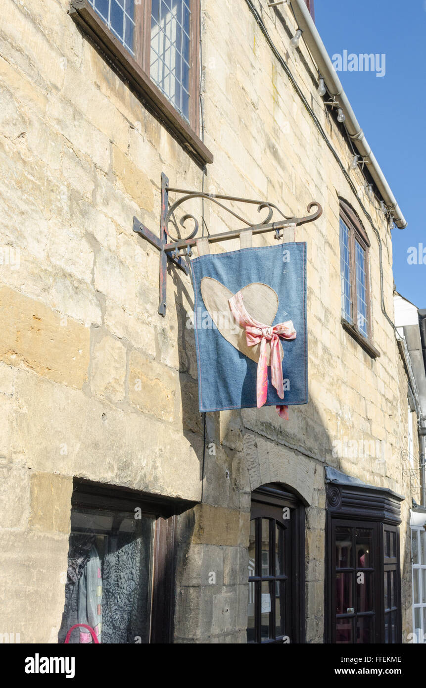 Decorative banner of straw boater with ribbon hanging outside a shop in Winchcombe, Gloucestershire - Stock Image