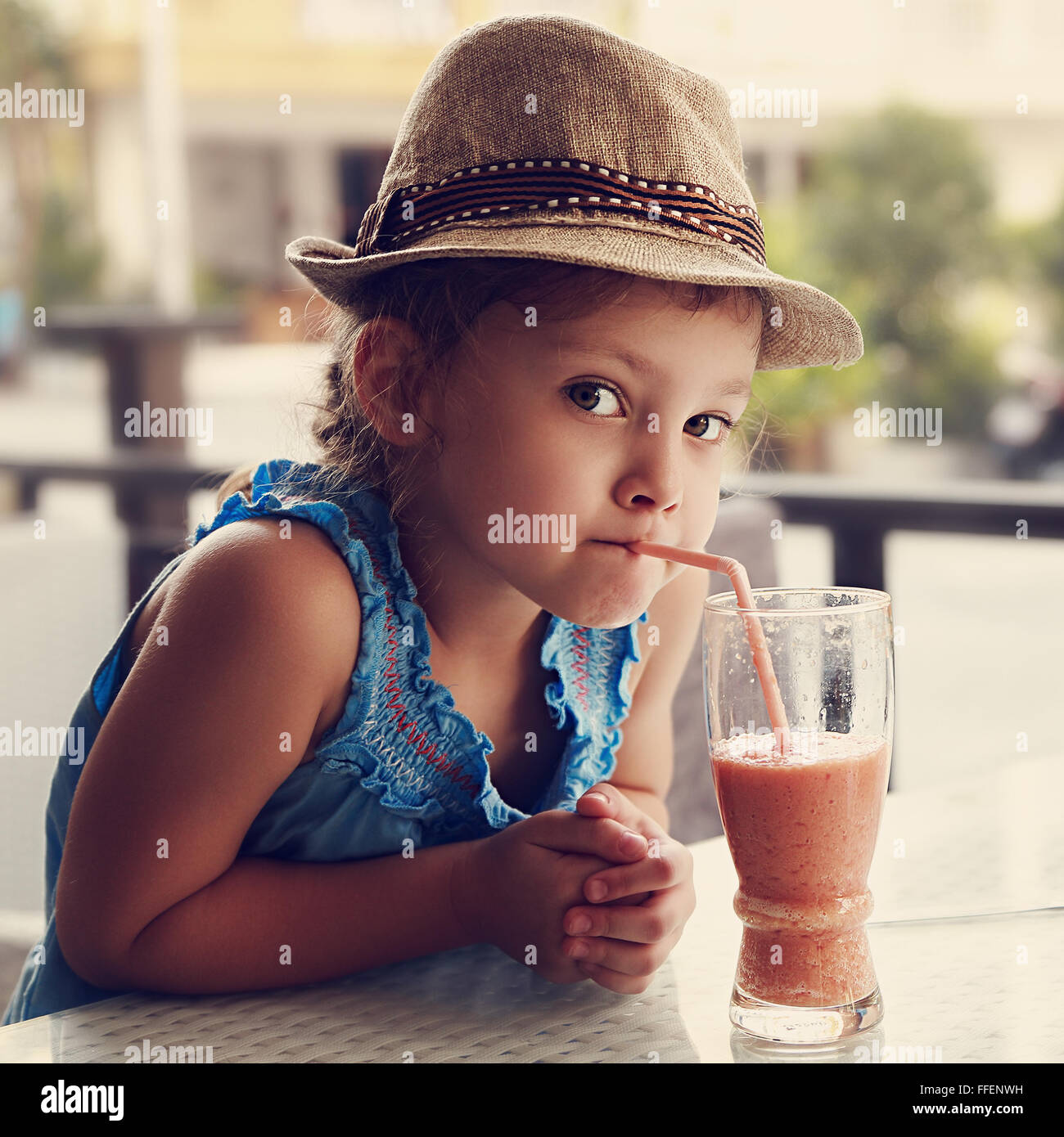 Curious fun cute kid girl in hat drinking tasty juice in summer street cafe. Closeup toned portrait - Stock Image