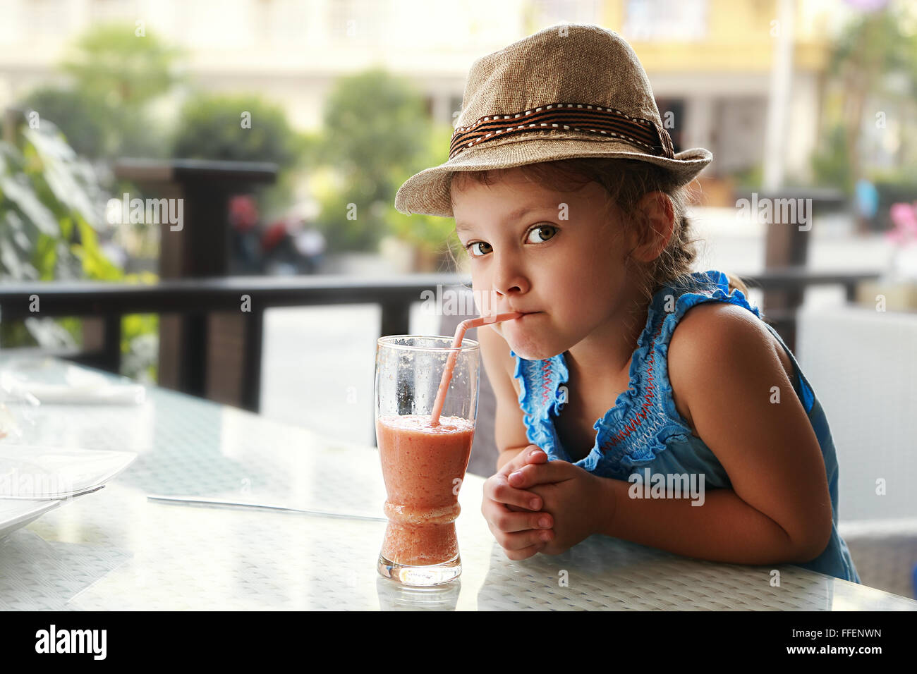 Curious fun cute kid girl drinking tasty juice in summer street cafe - Stock Image