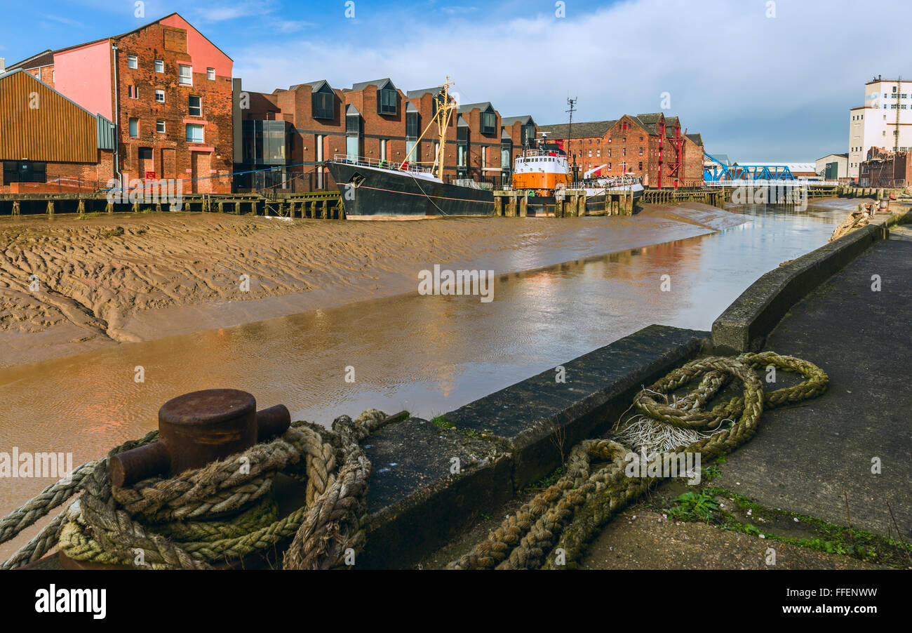 River Hull at low tide with an obsolete ship aground in the mud bank flanked by office and other buildings on one - Stock Image