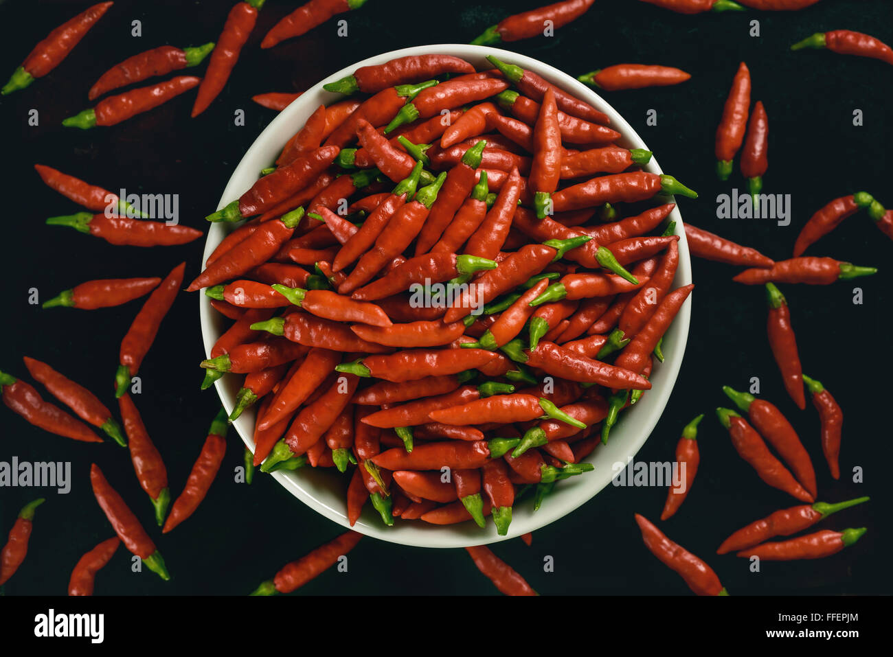 Red pepper in bowl on black background. - Stock Image