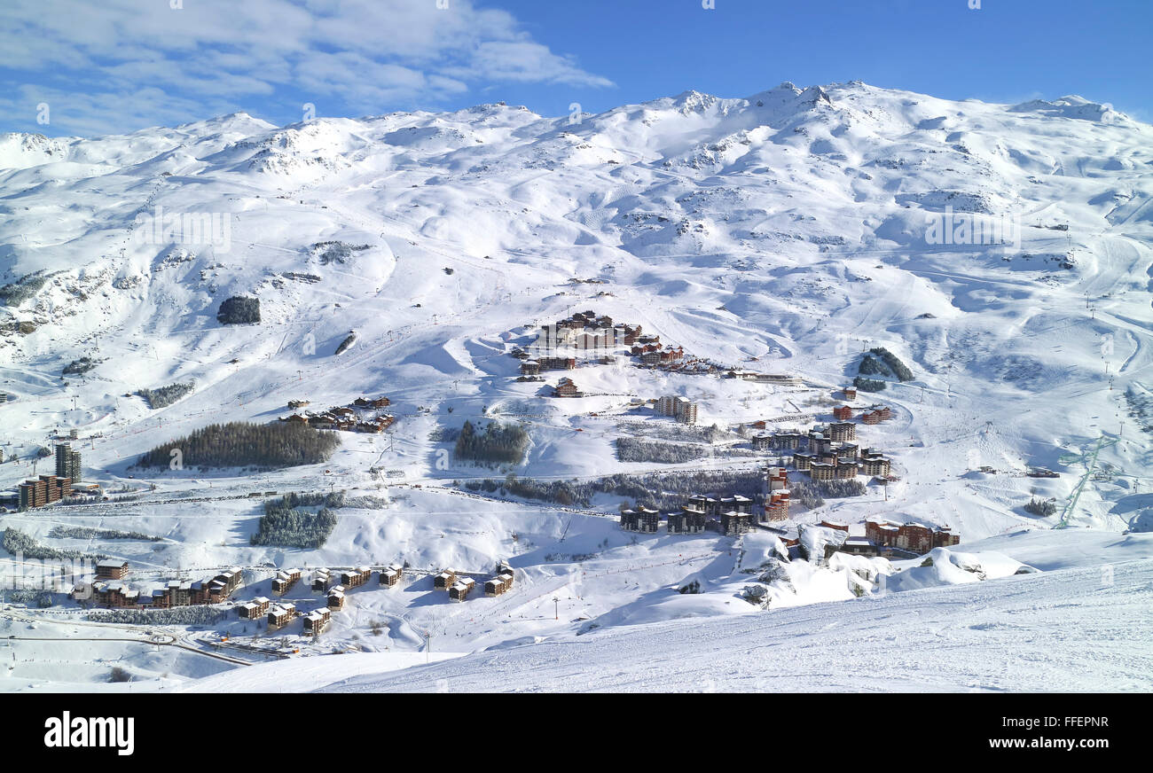 Aerial view of an alpine village, ski resort of Les Menuires, in 3 Valleys French Alps, with snowy slopes in high - Stock Image