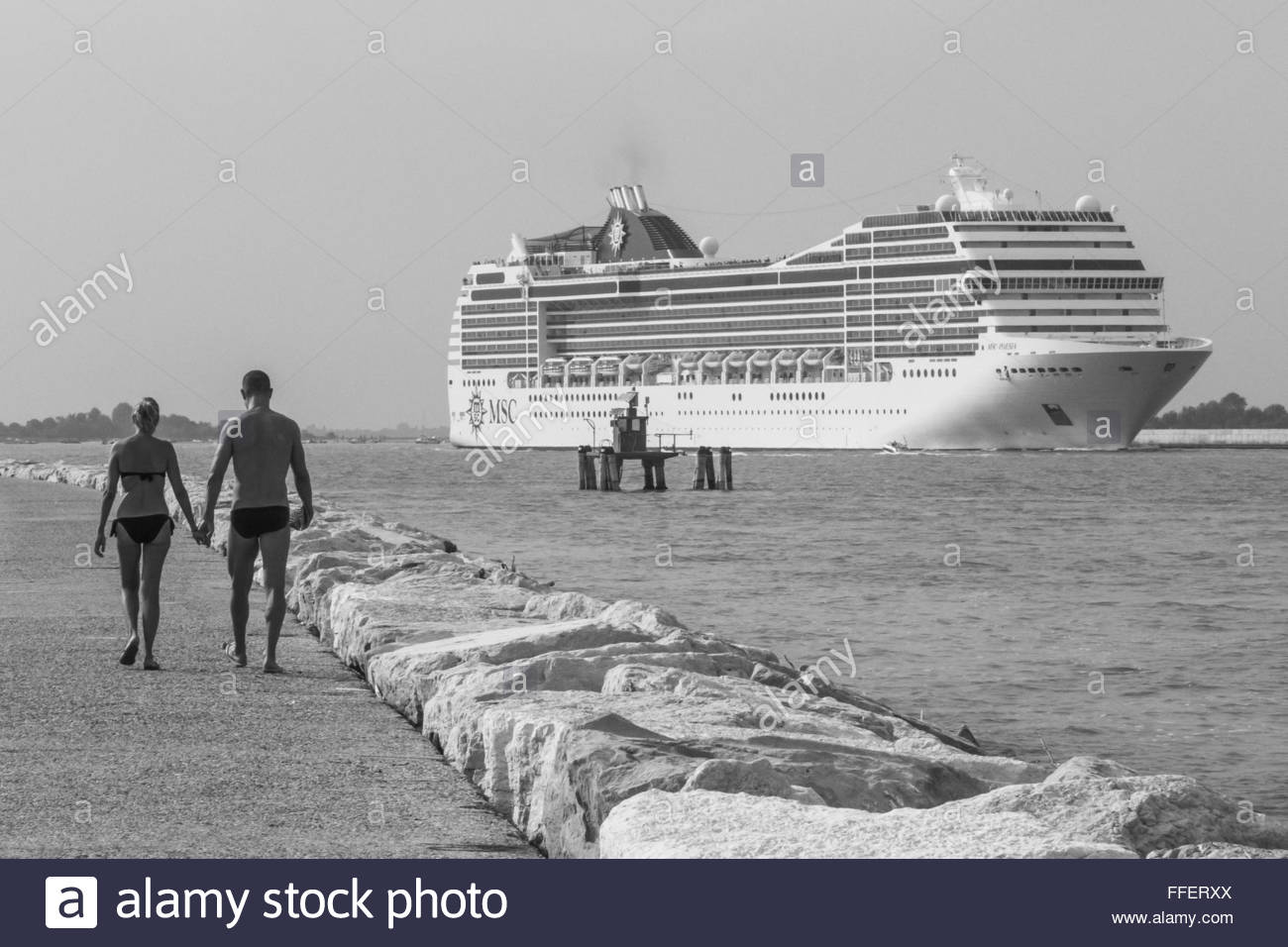 VENICE, ITALY -  15 AUGUST 2015:  Monochrome image of couple walking hand-in-hand along a headland with a cruise - Stock Image