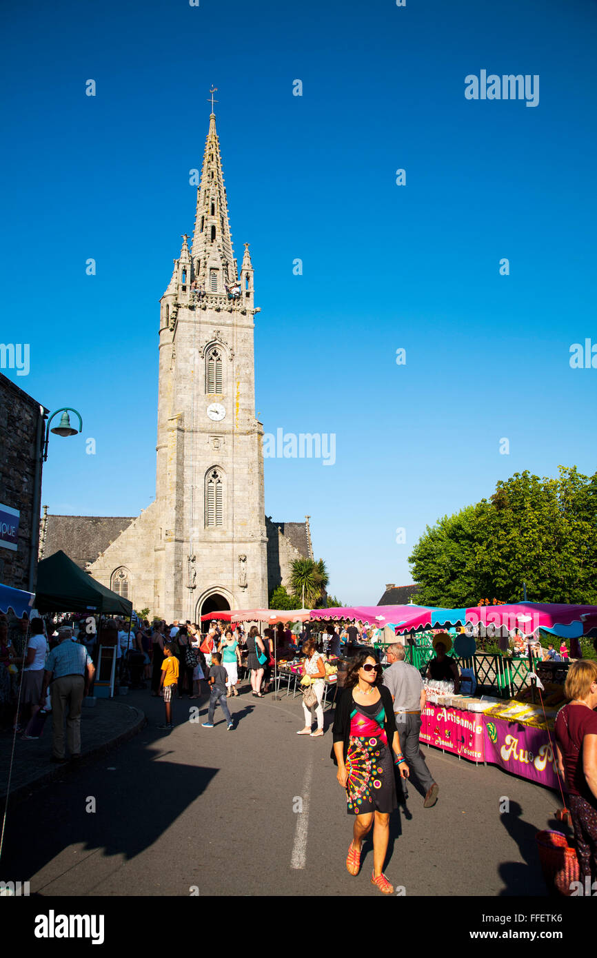 Abseiling from church spire above farmers market, Britany, France - Stock Image
