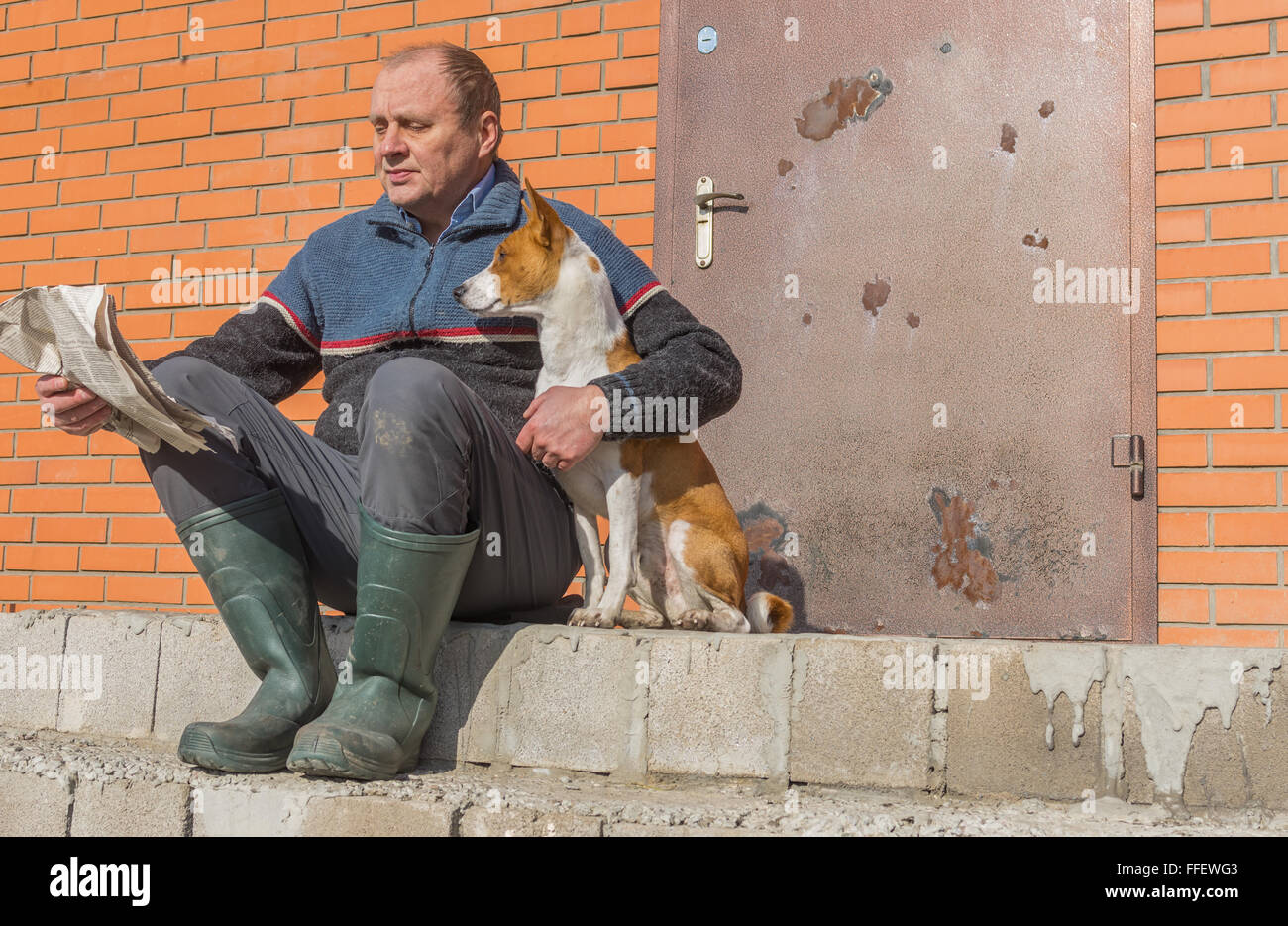 Young dog and mature man reading crumpled newspaper while sitting on a threshold at warm spring day - Stock Image