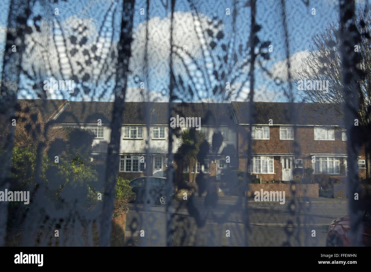View of houses across a street through a window with a patterned net curtain - Stock Image