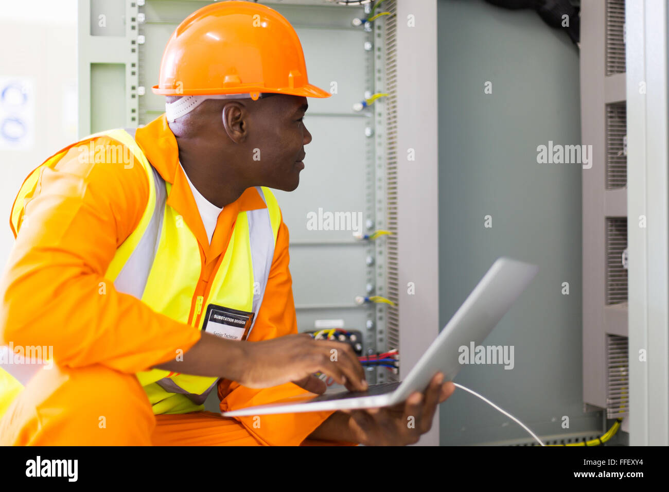 experienced senior African industrial technician checking machine status - Stock Image