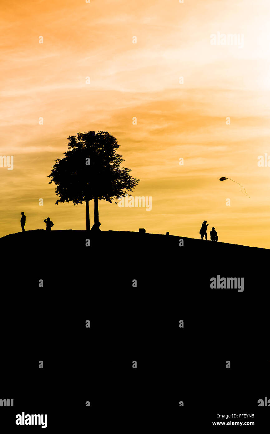 silhouettes of people on a mound, tree and a child flying a  kite at dusk - Stock Image