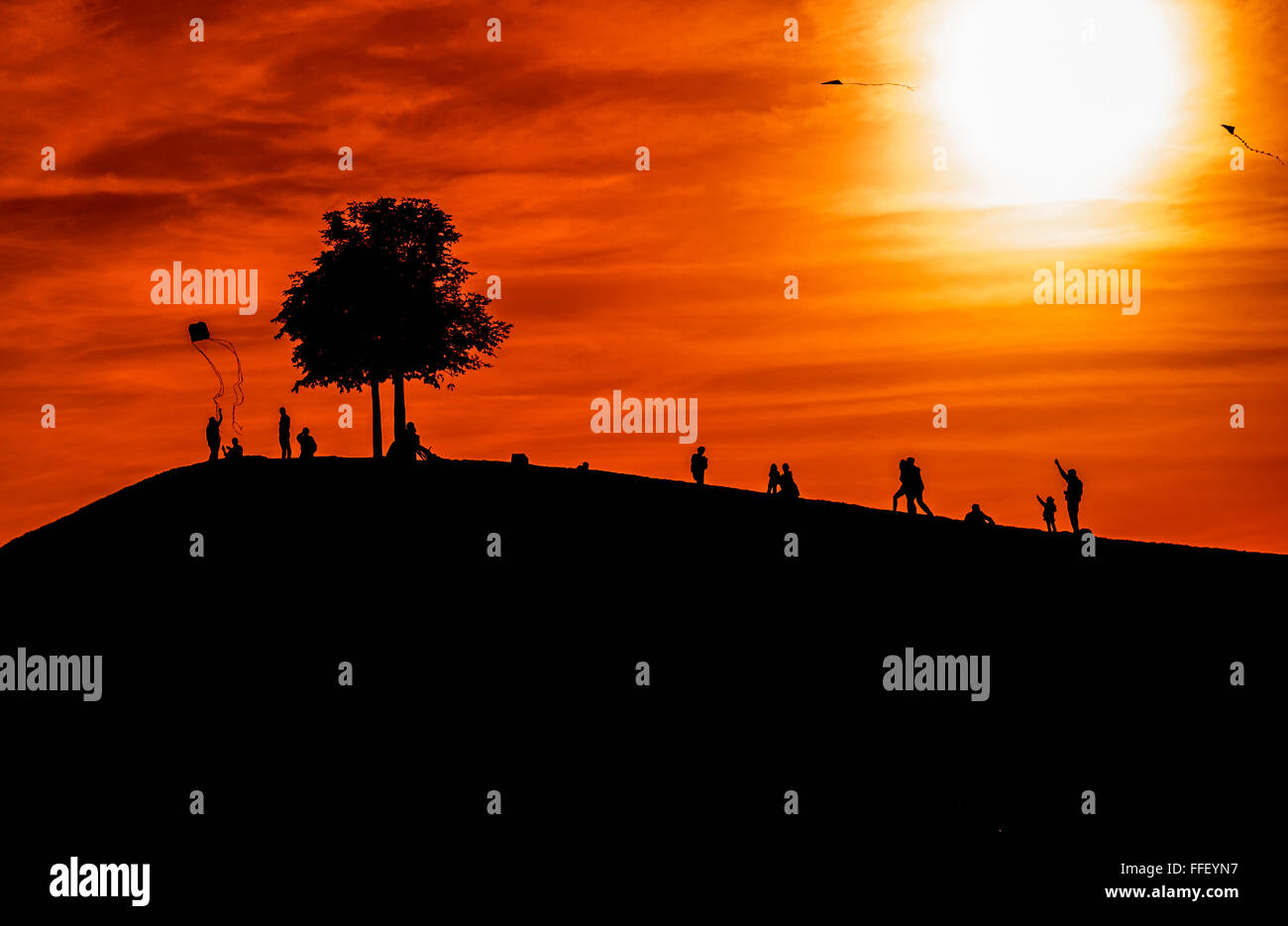 silhouettes of people on a hill, tree and various persons flying a kite at dusk - Stock Image