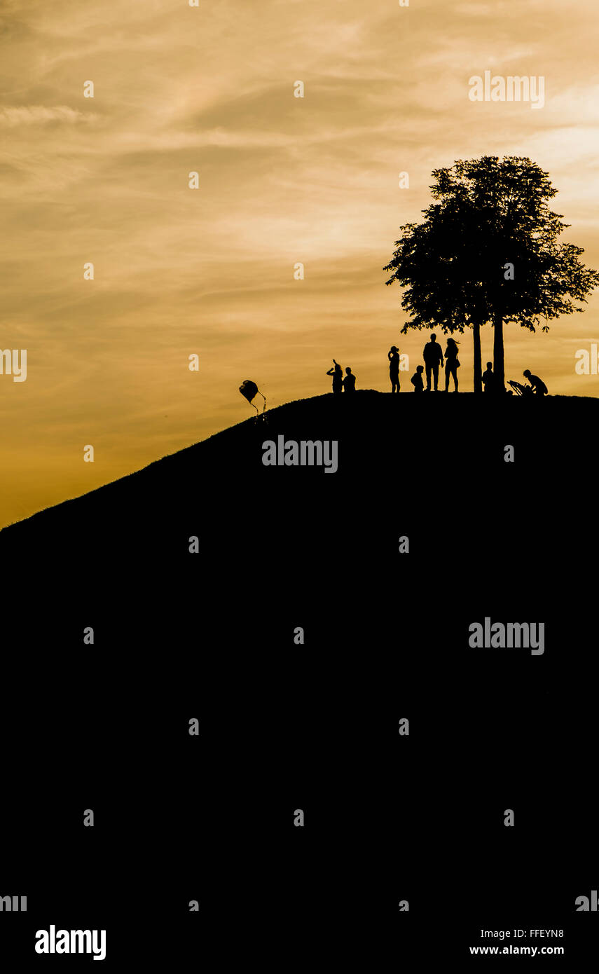 silhouettes of adults and children on a mound under a tree with kite at dusk - Stock Image
