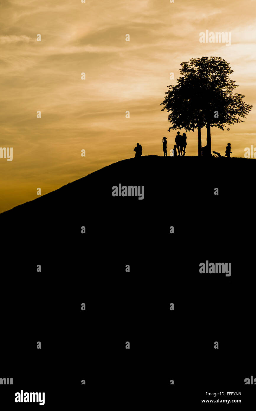 silhouettes of adults and children on a mound under a tree at dusk - Stock Image