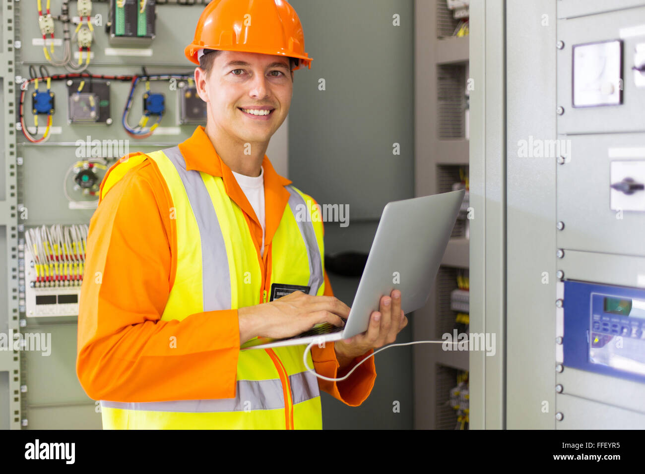 portrait of young technical using laptop computer - Stock Image