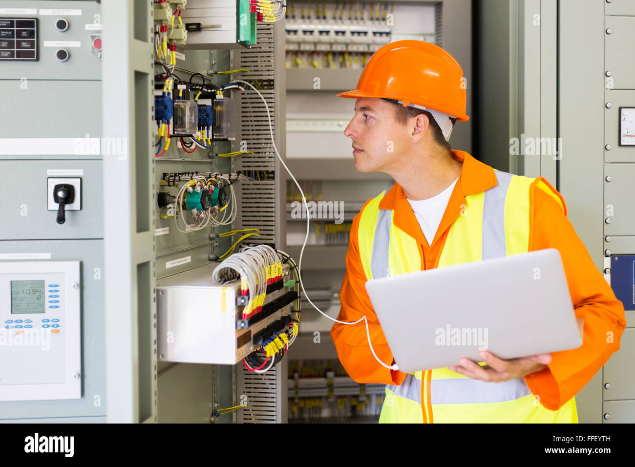 technician checking computerized transformer status with laptop computer - Stock Image