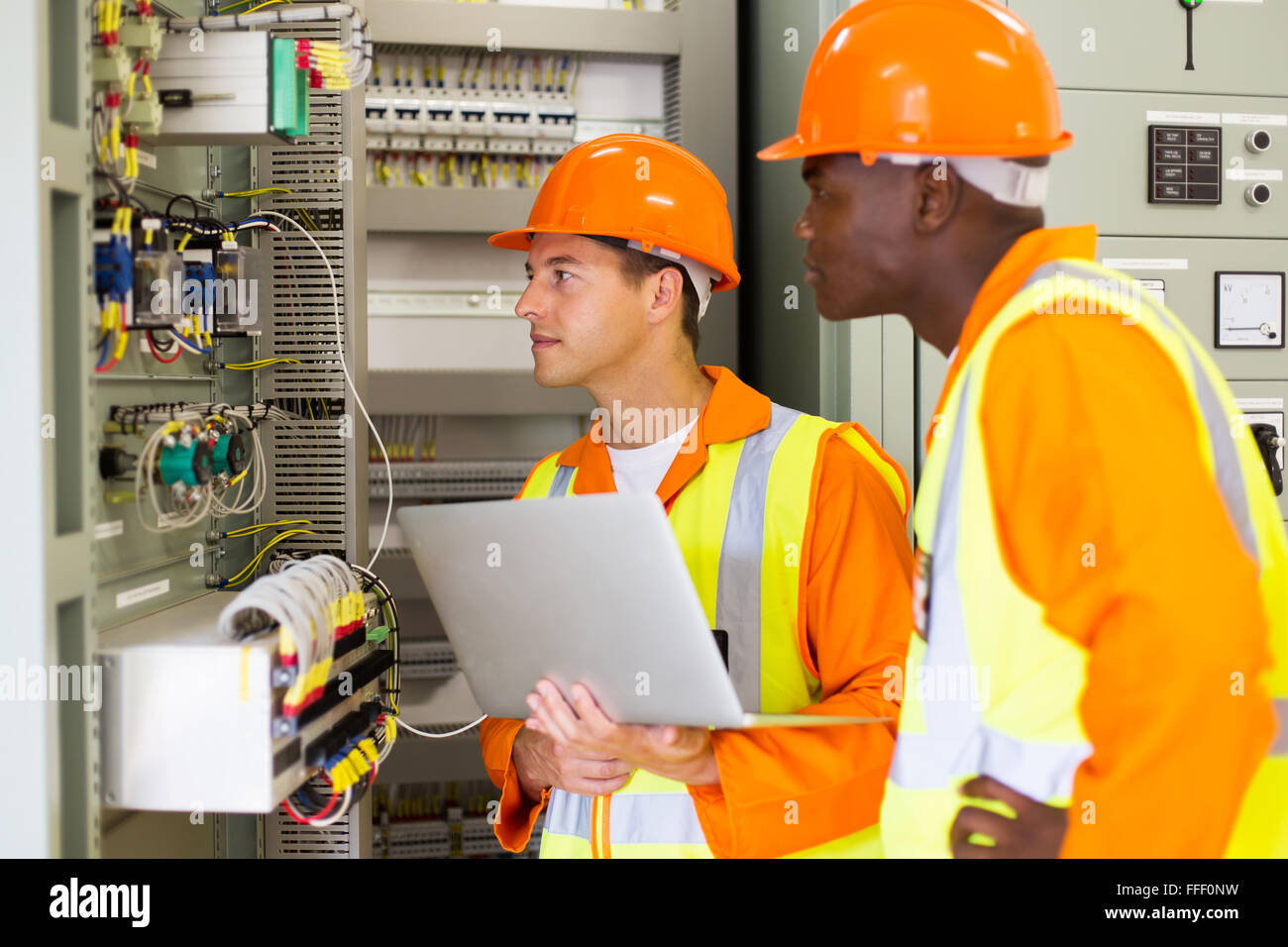 experienced multiracial industrial technicians checking transformer - Stock Image