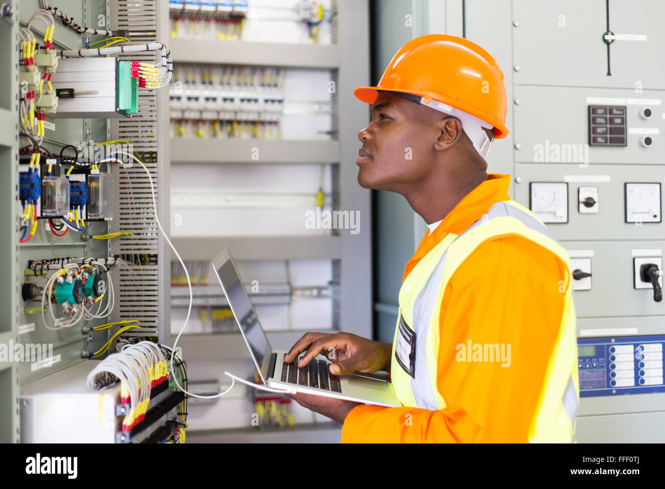 African industrial electrician working in power plant control panel Stock  Photo - Alamy
