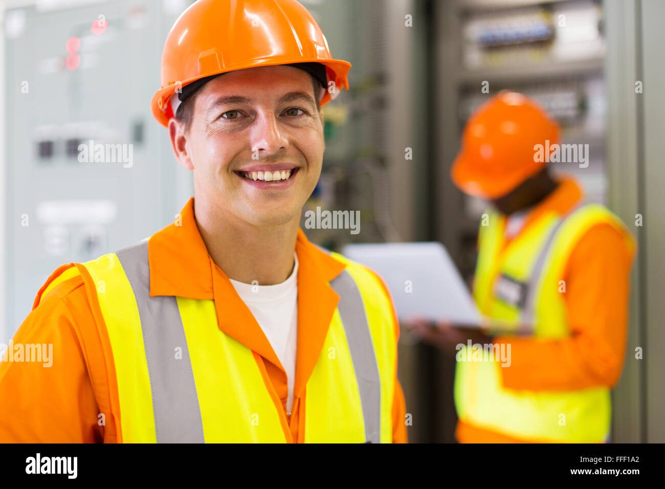 close up portrait of industrial technician in front of co-worker - Stock Image
