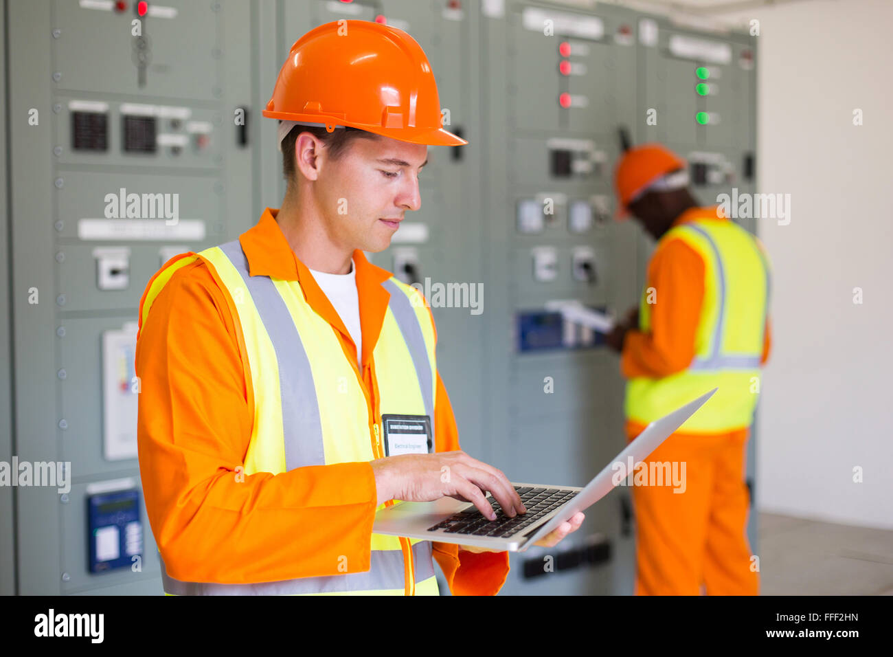 electrical worker working on laptop with colleague on background - Stock Image