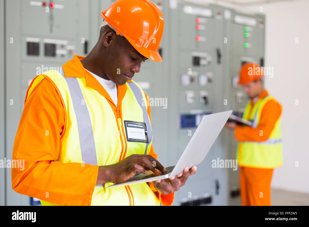 black technical worker using laptop with colleague on background - Stock Image