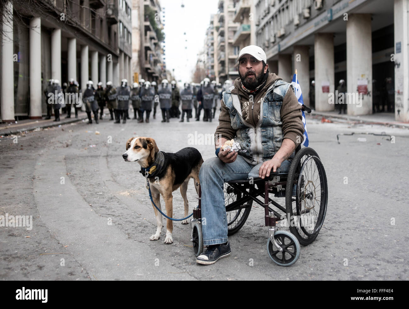 Athens, Greece. 12th Feb, 2016. A disabled man accompanied by his dog participates in a protest outside the Ministry - Stock Image